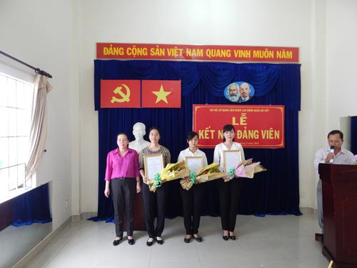 Bà Nguyễn Thị Bạch Yến (bìa trái), Bí thư Chi bộ Cơ quan LĐLĐ quận Gò Vấp, tặng hoa chúc mừng đảng viên mới