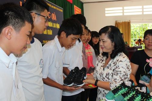 Bà Trần Kim Yến, Chủ tịch LĐLĐ TP HCM, trao quà cho con công nhân khó khăn