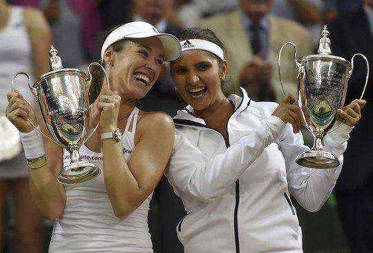 Mirza (phải) và Hingis nhận cúp vô địch đôi nữ Wimbledon rạng sáng 12-7 Ảnh: REUTERS