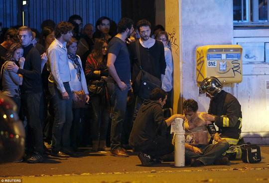 Lực lượng an ninh trợ giúp một người bị thương trên đường phố Paris đêm 13-11 Ảnh: REUTERS