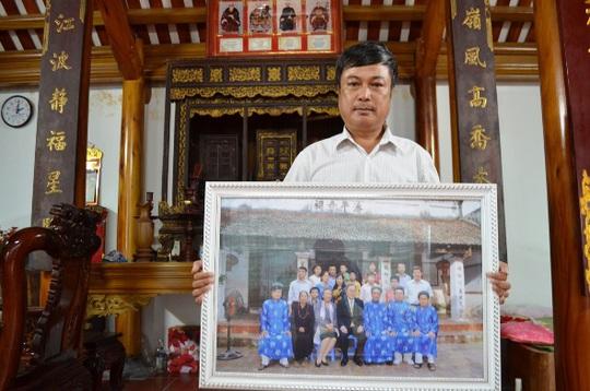 Ông Phan Huy Thanh cùng bức ảnh chụp với ông Ban Ki-moon trước nhà thờ họ Phan Huy