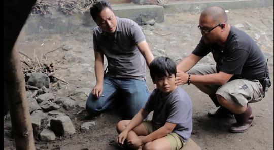 """Đạo diễn Victor Vũ (trái) hướng dẫn diễn xuất cho diễn viên nhí trên trường quay phim """"Tôi thấy hoa vàng trên cỏ xanh"""" (Ảnh do nhà sản xuất cung cấp)"""