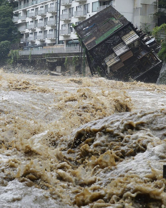 A building of an open-air spa, right, that belongs to Kinugawa Plaza Hotel, falls into the rapid stream of the Kinugawa River swollen by heavy rainfall in Nikko, Tochigi prefecture, northeast of Tokyo Thursday, 10 September 2015