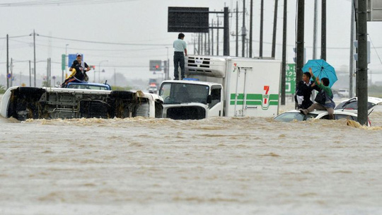 People wait for help as the vehicles are submerged in flooding in Joso, Ibaraki prefecture, northeast of Tokyo Thursday, 10 September 2015