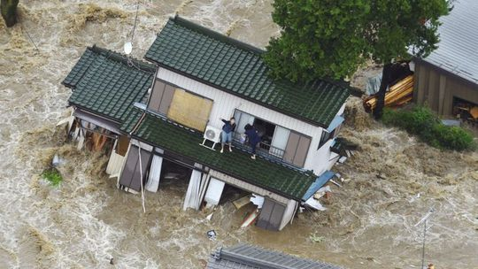 A person inside a house waves to a helicopter as the house is submerged in water flooded from a river in Joso, Ibaraki prefecture, northeast of Tokyo Thursday, 10 September 2015