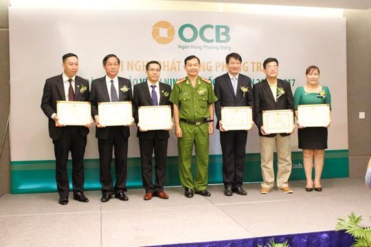Đồng chí Đại tá Đinh Thanh Nhàn – Phó Giám đốc Công An TP HCM trao giấy khen cho các tập thể và cá nhân tại OCB có thành tích trong Phong trào toàn dân bảo vệ an ninh Tổ quốc