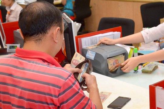 Giao dịch tại một ngân hàng ở TP HCM Ảnh: Tấn Thạnh