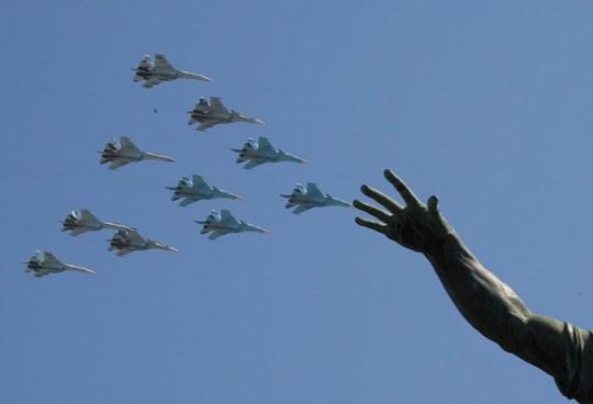 Các chiến đấu cơ SU-34, SU-27 và máy bay đa nhiệm SU-35S bay qua một bức tượng ở Quảng trường Đỏ. Ảnh: EPA