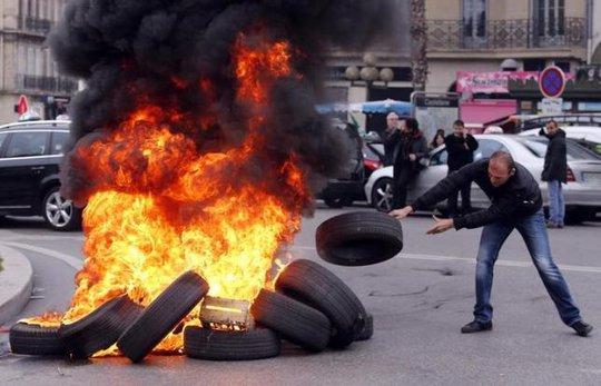 Người biểu tình đốt lốp xe phản đối Uber hôm 26-1. Ảnh: Reuters