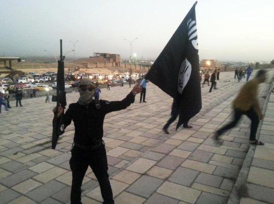 Một chiến binh IS cầm cờ tại TP Mosul. Ảnh: Reuters