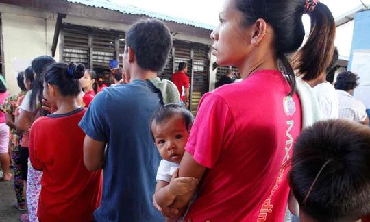 Một phụ nữ bế con tới địa điểm bỏ phiếu ở TP Davao sáng 9-5. Ảnh: REUTERS
