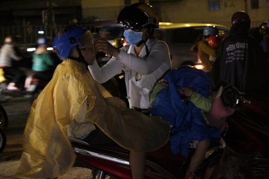 Chị Huyền Trang mặc áo mưa cho con trước khi cơn mưa ập đến. Chị cho biết: Khoảng 3 giờ chiều, tôi đến khu vực Tiền Giang thì bắt đầu kẹt xe nặng. Tới gần thành phố kẹt xe giảm hơn một chút thì lại bị mưa.