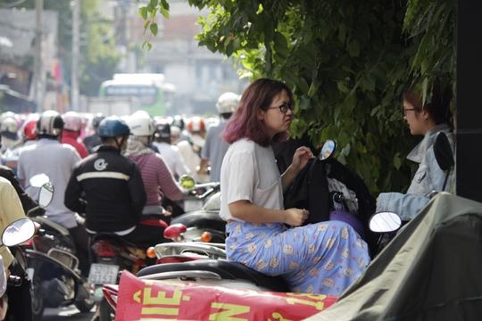 """Hai cô gái tấp lại bên đường chờ tình trạng kẹt đường thuyên giảm mới đi tiếp. Chị Minh Trang chia sẻ: """"Sáng này 7 giờ dậy, ra đường đi làm như mọi ngày thì giật mình vì kẹt xe kinh khủng. Vậy làn mình tấp vào đây ngồi chơi đợi trưa rồi qua cơ quan luôn""""."""