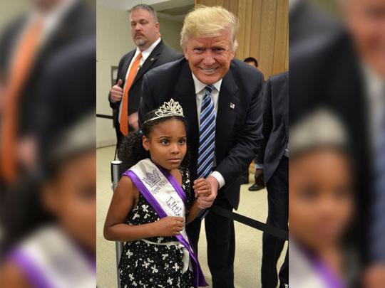 Bé gái sợ hãi khi đứng gần ông Trump. Ảnh: TWITTER