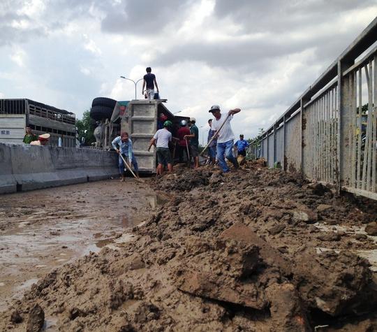 Hàng tấn bùn đất đổ tràn trên làn đường xe máy cầu Phú Mỹ