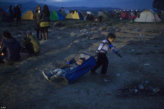 Trẻ con chơi đùa tại trại tị nạn sát biên giới Macedonia. Ảnh: AP