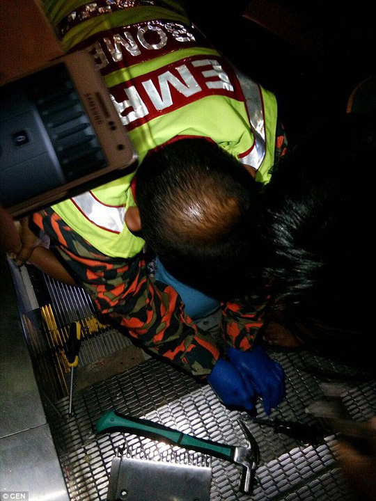 Lực lượng cứu hộ tháo thang cuốn để cứu cậu bé. Ảnh: CEN