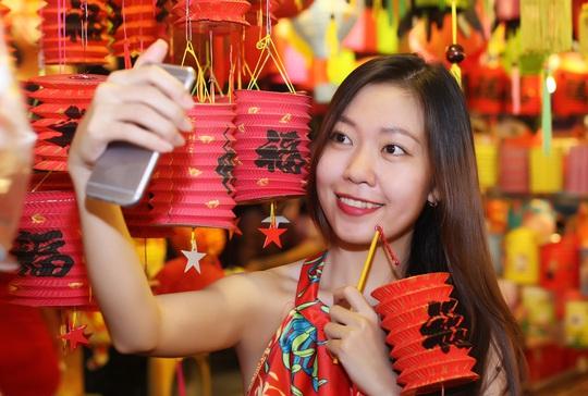 Bạn Diễm Linh, sinh viên Trường Cao đẳng Văn hoá Nghệ thuật và Du lịch Sài Gòn, thích thú ghi lại khoảnh khắc cùng chiếc lồng đèn đỏ