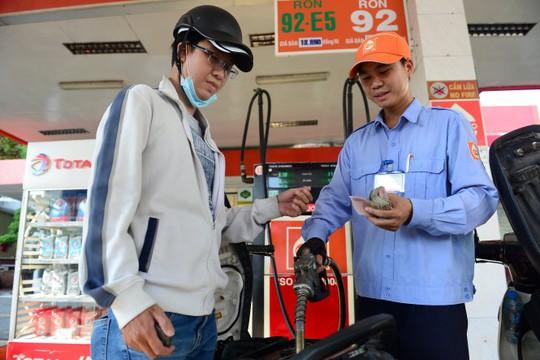 Anh Nguyễn Việt Đức (Q.Bình Thạnh, TP HCM) chọn đổ xăng E5 vì có giá thấp hơn các loại xăng khác - Ảnh: Quang Định