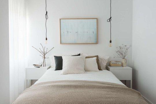 Giường ngủ êm ái, hai bên là táp đầu giường và đèn thả đối xứng.