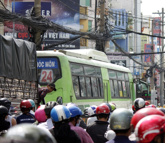 Thấy con đường tê liệt quá lâu, tài xế xe tải nóng ruột leo qua cửa để nhìn về phía sau.