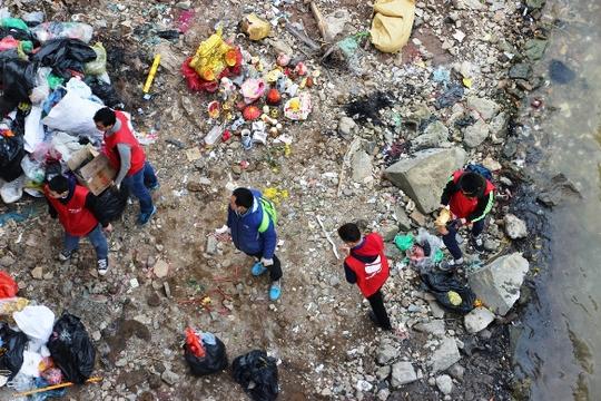 Phía dưới chân cầu, một tổ túc trực tại đây thu gom, phân loại rác, hoá chân hương, bàn thờ cũ...