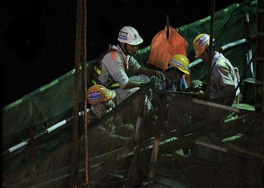 Một nhóm công nhân tăng ca vào ban đêm đang bàn bạc công việc trước khi bắt tay vào làm việc tại dầm cầu Metro ở sông Sài Gòn.