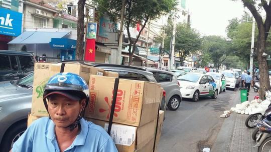 Một người chở hàng lấn trái sang dòng xe ô tô để mong vượt qua kẹt xe