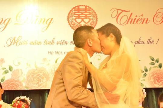 Hai vợ chồng anh chị hôn nhau trong sự hò reo của phấn khích của mọi người