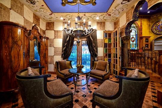 Phòng khách chính vương giả với những bức tường ốp đá, nội thất gỗ trạm khác tinh xảo, được thông dẫn đến khu vườn riêng trong lâu đài.