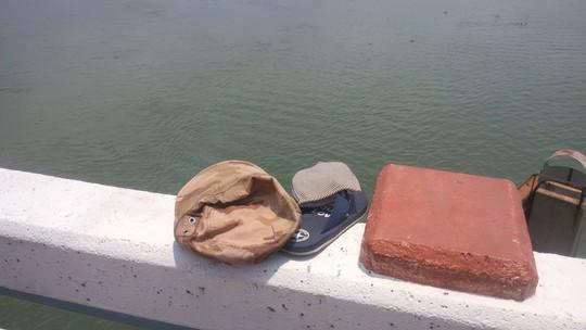 Mũ và dép của thanh niên trên thành cầu