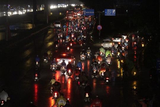 Kẹt xe trong mưa, lại phải đi trong bóng tối khiến nhiều người hết sức ngao ngán và mệt mỏi. Trong ảnh: Giao lộ Võ Văn Kiệt - Quốc lộ 1 vào lúc 21 giờ vẫn náo nhiệt.
