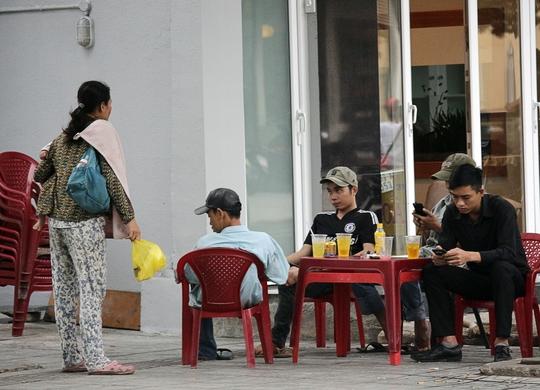 Một người phụ nữ khỏe mạnh bế theo một em bé xin tiền dọc đường Trần Nhân Tôn, quận 5 (gần giao lộ Trần Nhân Tôn - Nguyễn Chí Thanh - Hùng Vương).