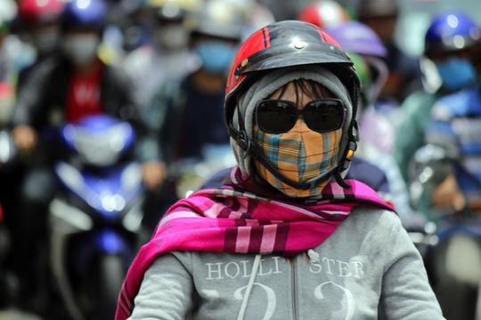 Một phụ nữ với trang phục kín mít để đối phó với nắng nóng và khói bụi.