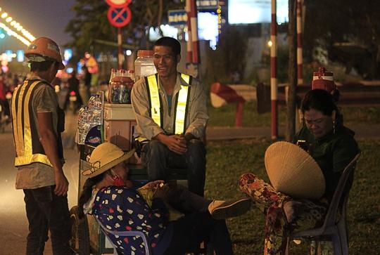 Hai người thợ tranh thủ nghỉ ngơi, trò chuyện với những người bán nước trước khi tăng ca vào ban đêm.