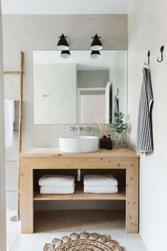 Gương soi cỡ lớn, tủ gỗ lưu trữ và chiếc thang treo khăn tắm độc đáo.