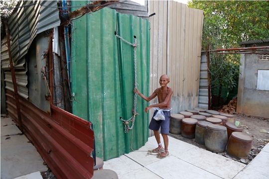 Cánh cửa chính vào nhà ông được trang bị hệ thống dây xích và khóa kỳ cục. Khóa trên, khóa dưới