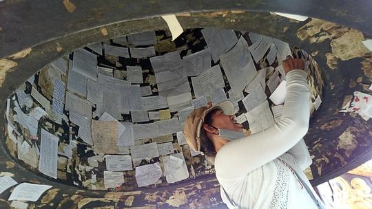 Sau khi đốt nhang, nhiều người sử dụng những tấm giấy viết tên rồi dán khắp chuông chùa để cầu an.
