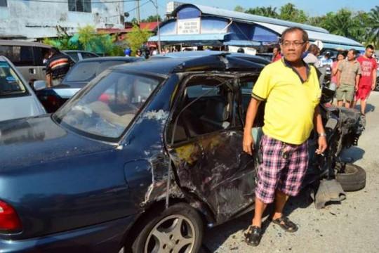 Chủ sở hữu một chiếc ô tô gặp nạn ngẩn người đứng nhìn. Ảnh: The Star