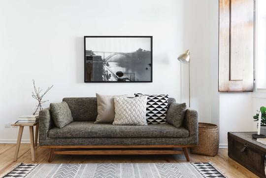 Phòng khách khá giản dị với bộ sofa màu xám trung tính.