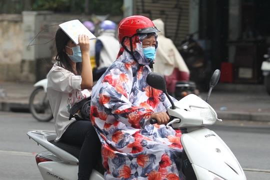 Gần đến giờ thi trời đổ mưa, nhiều thí sinh được phụ huynh vội vã chở đến điểm thi. Ảnh: Hoàng Triều