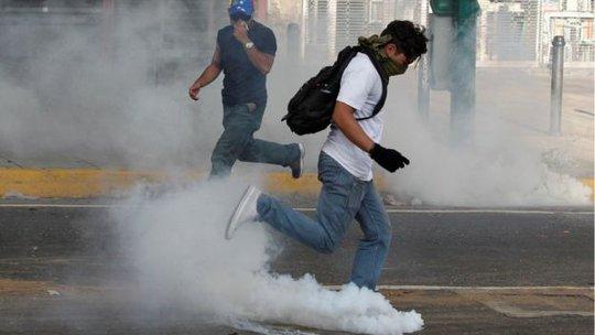 Người biểu tình đụng độ cảnh sát ở Caracas. Ảnh: REUTERS