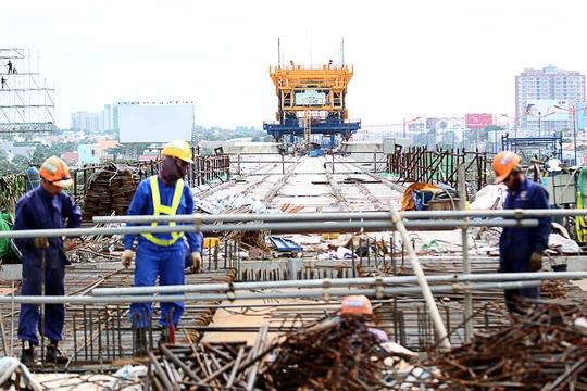 Các công nhân đang tất bật thi công các hạng mục tại nhà ga ngã tư Bình Thái. Phía xa, hệ thống đà giáo di động đã lắp ghép kết nối các nhịp cầu vào nhà ga ngã tư Bình Thái.