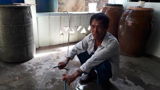 Ông Sáu đang nối ống dẫn nước của gia đình ra bồn nước đặt trên xe của Huyện đội Kiên Hải.