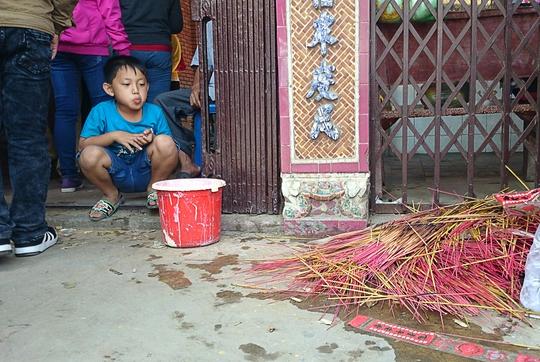 Một đứa trẻ nhìn đống nhang cháy dở của khách hành hương để lại trước cửa chùa.