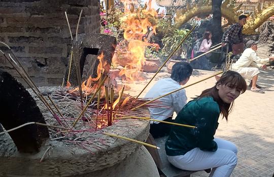 Khi đã không còn chỗ nào để cắm nhang, nhiều người cho các bó lớn vào giữa bệ hương và đốt cháy.