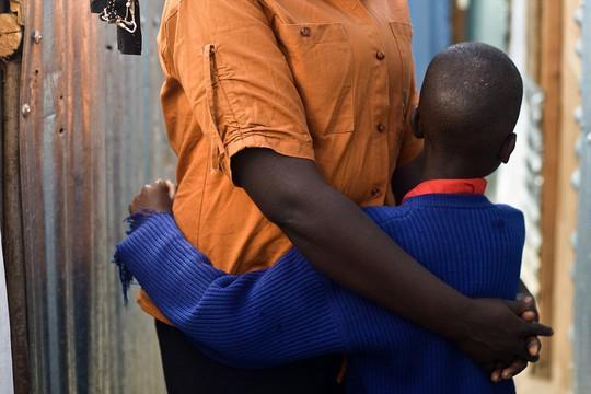 Nyasiongo F., 24 tuổi, đứng bên ngoài ngôi nhà thuộc một khu ổ chuột ở Nairobi cùng con trai 7 tuổi. Ảnh: HRW
