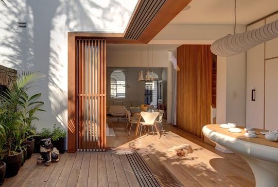 Sân vườn như hòa nhập vào trong căn nhà với thiết kế cửa gỗ cuốn sáng tạo, hiện đại.