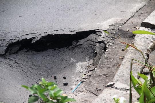 Dưới đoạn đường bị nứt, lún có nhiều vết nứt lớn nham nhở, bị khoét hàm ếch và có dấu hiệu tiếp tục sụt lún