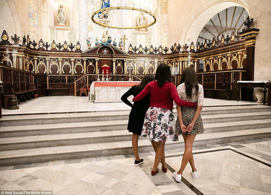 Đệ nhất phu nhân Michelle Obama ôm hai cô con gái trong một nhà thờ. Ảnh: White House